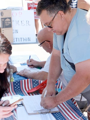 Mark Huff of Sturgis signs a petition seeking to put a state Constitution amendment to regulate, define and limit government power on the November ballot, at a rally Saturday in Sturgis. The petition needs 550,000 signatures to become a ballot item.