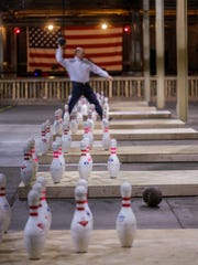 A man tosses a football at bowling pins on the other