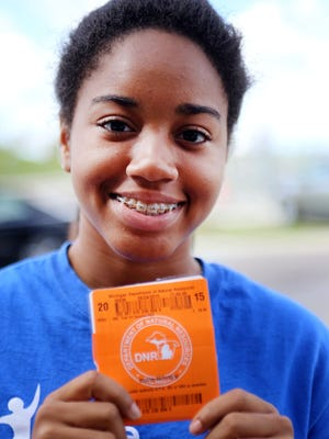 Cartonise Lawson-Wilson, 17, of Grosse Pointe Farms shows off her first fishing license that she receives at the end of  the six-week, inaugural DNR Youth Conservation Academy held at the DNR Outdoor Adventure Center in Detroit.  She says the academy opened her eyes to many opportunities, but she remains interested in political science for her future. She is a rising junior at the Arts Academy in the Woods in Fraser.
