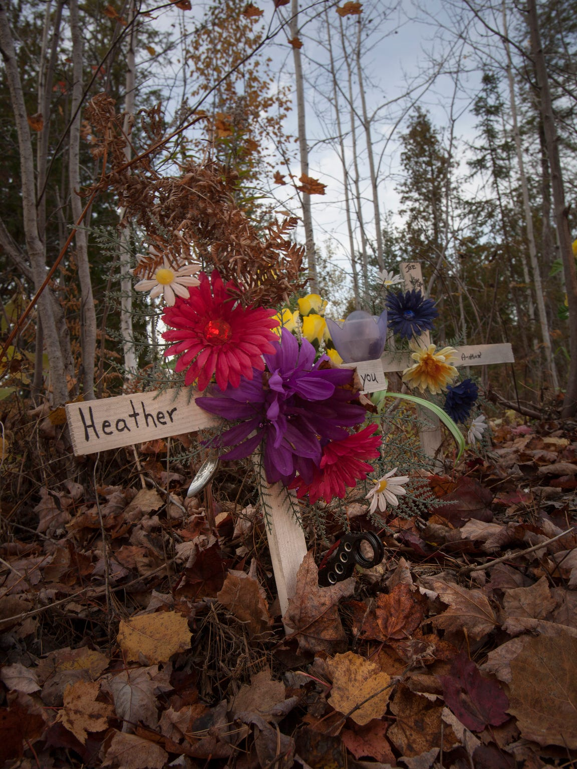 A makeshift memorial stands in honor of Jody Hutchinson, 42, and sisters Carrie Nelson, 31, and Heather Aldrich, 25, at the side on River Road in Doyle Township where their bodies were burned in an SUV..