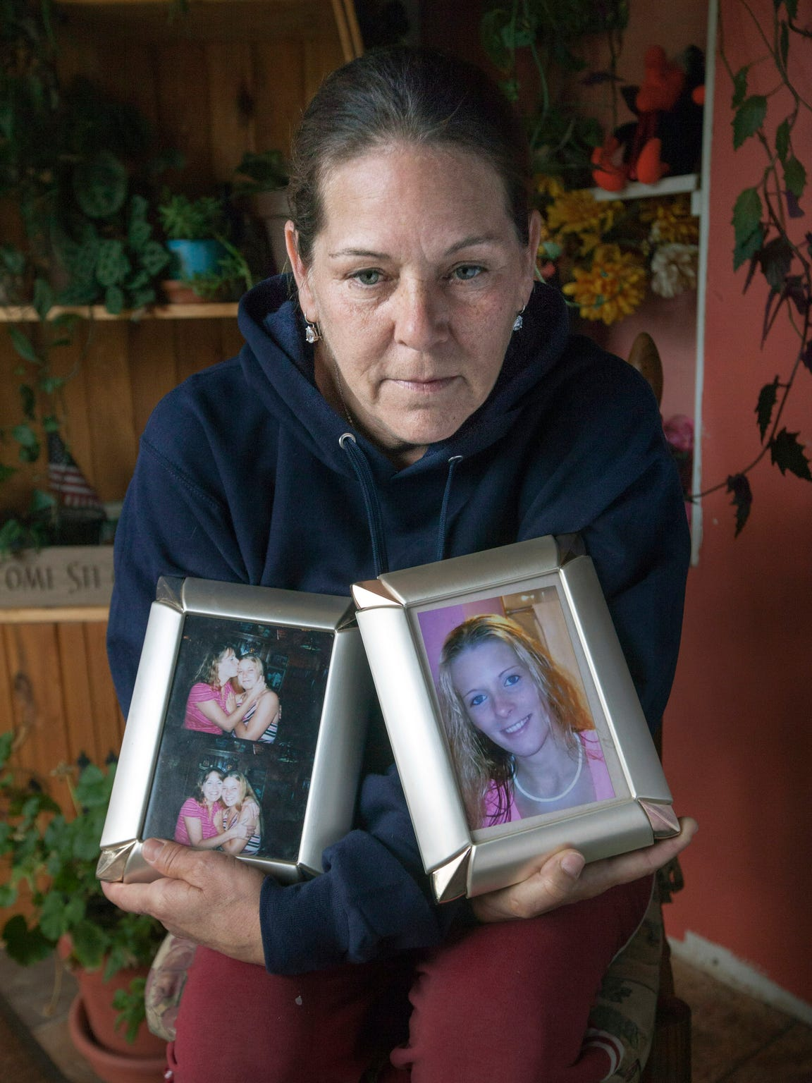 Kellie Roll of Germfask holds family photos of her daughters Carrie Nelson, 31, and Heather Aldrich, 25, who were murdered in mid April, along with Nelson's boyfriend Jody Hutchinson, 42.