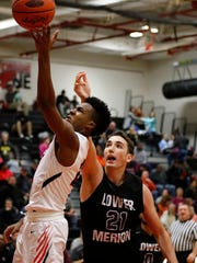 William Penn's Montrel Morgan gets around Lower Merion's Jeremy Horn for a layup during Monday's game at the J.P. McCaskey holiday tournament in Lancaster. The Aces defeated the Bearcats, 58-55.