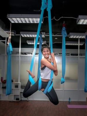 Mia Sara Malabanan, and aerial intermediate student, demonstrates an aerial pigeon pose at Mantrasana Fitness Studio.