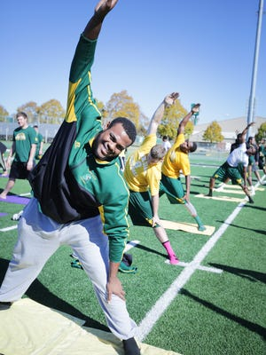 Sam Tate, 22,  a sophomore left tackle, participates in yoga with the rest of his Wayne State University football team Sunday, Oct. 25, 2015 at Adams Field on Wayne State University's  campus.