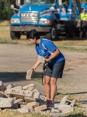 Harper Creek Community Schools Board of Education President Vikki Bauer grabs a couple of bricks from the demolition of the former Wattles Park Junior High School on Monday.