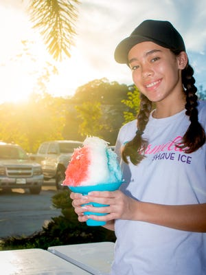 Mikaila Genereux of Marmela's Shave Ice holds up their Holy Mac, fluffy ice topped with syrup and coconut with ice cream.