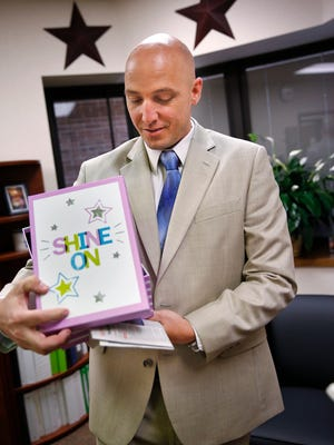 """New principal Jered Pennington shows a present from the second grade team at Amy Beverland Elementary School on Tuesday, Aug. 23, 2016.  On the box is his signature saying, """"Shine On!""""  He was named the school's new principal, filling the role left vacant after its previous principal, Susan Jordan, was killed in a tragic accident when a bus jumped the curb and hit her during school dismissal  in January  2016."""