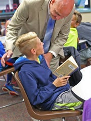 New principal Jered Pennington talks with student Jack Bilyeu at Amy Beverland Elementary School on Tuesday, Aug. 23, 2016.  Pennington was named the school's new principal, filling the role left vacant after its previous principal, Susan Jordan, was killed in a tragic accident when a bus jumped the curb and hit her during school dismissal, in January  2016.  He visits the classrooms daily and works to have positive interactions with the kids.
