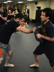 "Jason Toledo uses Patrick Riley as a punching bag in the ""overwhelming violence"" exercise. A dozen students participated in a Krav Maga self defense class at Training Grounds Martial Arts Academy in Bonita Springs."