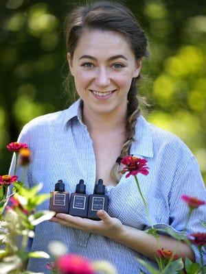Megan Cox shows some of her products in Bedford, Ind. In 2016, she has introduced Farm to Face, a totally home-grown, hand-crafted line of face oils. Her company now is called Amalie.