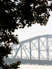 In this Wednesday, Nov. 16, 2016 photo, walkers cross the Walnut Street Pedestrian Bridge a  smoke from wildfires fill downtown Chattanooga, Tenn., and the Tennessee Valley with a pungent haze as seen from the North Shore area of Chattanooga. (Dan Henry/Chattanooga Times Free Press via AP)