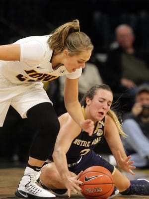 Iowa's Kathleen Doyle, left, and Notre Dame's Marina Mabry fight for a loose ball during their game at Carver-Hawkeye Arena on Wednesday, Nov. 30, 2016.