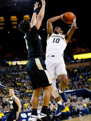 Michigan guard Derrick Walton Jr. (10) shoots defended by Purdue guard Carsen Edwards (3) in the first half Saturday in Crisler Center.