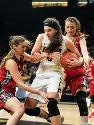 Iowa's Megan Gustafson fights off South Dakota defenders during their WNIT second round game at Carver-Hawkeye Arena on Saturday, March 18, 2017.