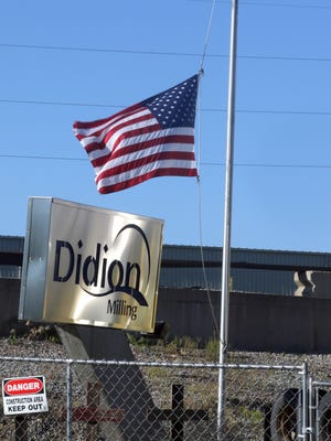 A flag flies at half mast in front of the rubble left from a May 31 explosion at a corn mill plant at the Didion Milling complex in Cambria resulted in the death of five workers and injury to 12 others. OSHA found Didion at fault and proposed more than $1.8 million in fines.