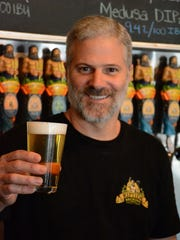 Partner Norm Scherner hoists a cold one at Riptide Brewing Co.'s taproom. Microbreweries have sprung up in Southwest Florida, making the area part of the craft beer wave sweeping the nation.