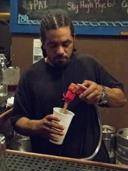 Employee Jonathan Thomas serves a drink at Arcadia in Battle Creek Saturday night.