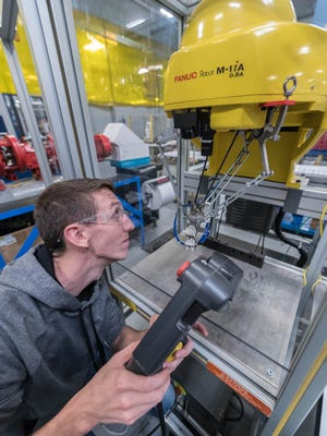 Chris DeShon works with a Fanuc robot at the Regional Manufacturing Technology Center on Thursday, Oct. 12, 2017.