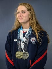 Emily Weiss poses for a picture at her home, wearing the medals she earned at FINA world junior swimming championships in August 2017, seen in Yorktown, Nov. 1, 2017.