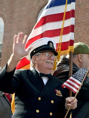 U.S. Navy veteran Bobby Smith, 82, from Maryville waves to the Knoxville area residents filling the side walks on Gay Street for Knoxville's 92nd Veterans Day Parade on Friday, Nov. 10, 2017.