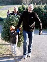 The Zarling families, grandfather Russ (back), Mack, 3, and Jake, of Waukesha, carry their choice of Christmas tree to the register at Cozy Nook Farm, Waukesha, on Nov. 24, while mom and grandma follow. It's a tradition for many families to purchase their Christmas trees at the farm the day after Thanksgiving.