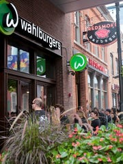 People lined the sidewalk eager to be first to eat at Mark Wahlberg's Wahlburgers during the  grand opening in downtown Detroit's Greektown on Monday, August 15, 2016.