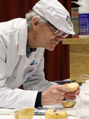 Dieter Koch-Hartke, from DMK Dairies in Germany, examines a smoked soft and semi-soft cheese entry during the World Championship Cheese Contest in Madison on March 7, 2018.