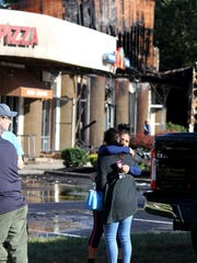 People embrace at the scene of an overnight fire at