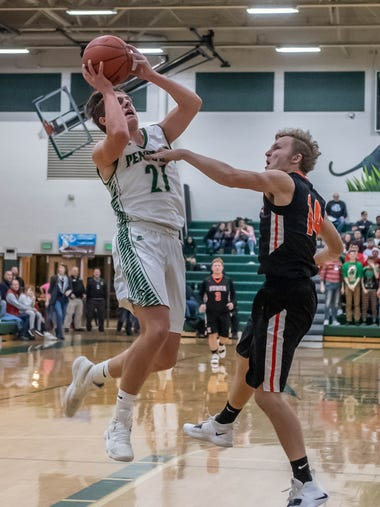 Pennfield's Shawn Gardner (21) goes for the hoop against