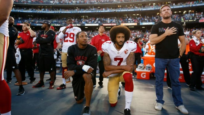 San Francisco 49ers quarterback Colin Kaepernick (kneeling, right) has sparked national debate with his anthem protests.