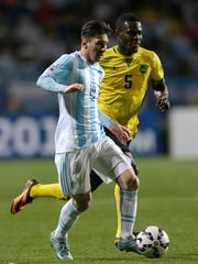 Argentina's Lionel Messi, front, dribbles the ball as he is chased by Jamaica's Lance Laing, during a Copa America Group B soccer match at the Sausalito Stadium in Vina del Mar, Chile, Saturday, June 20, 2015. (AP Photo/Ricardo Mazalan)
