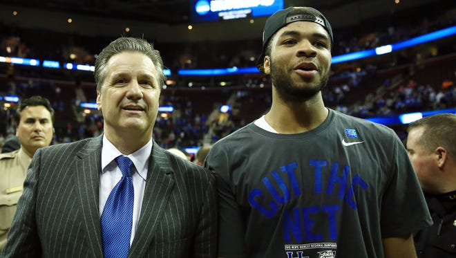 Kentucky coach John Calipari and guard Andrew Harrison (right) walk off the court after the Wildcats beat Notre Dame 68-66 in the Midwest Region final Saturday in Cleveland.