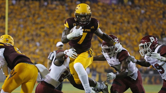 ASU's Karen Ballage (7) hurdles the arms of New Mexico State's Shamad Lomax (22) on his way to a touchdown during the first quarter at Sun Devil Stadium in Tempe, Ariz. on August 31, 2017.