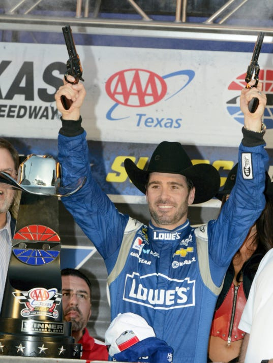 Jimmie Johnson fires pistols in victory lane after winning the NASCAR Sprint Cup series race Sunday at Texas Motor Speedway in Fort Worth, Texas.