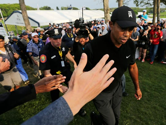 Golf fans reach out to Tiger Woods as he walks to the 18th tee during the second round of the PGA Championship golf tournament, Friday, May 17, 2019, at Bethpage Black in Farmingdale, N.Y. (AP Photo/Charles Krupa)