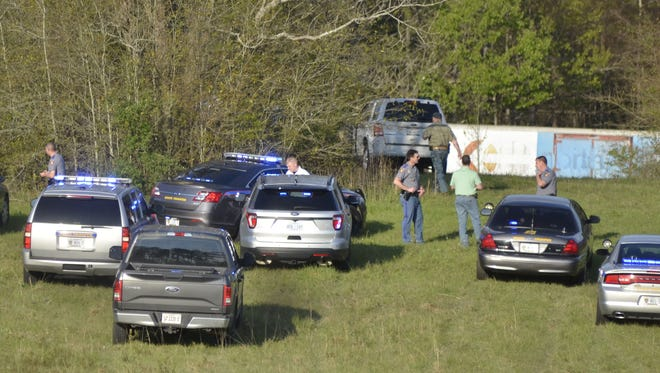 Law enforcement officers investigate the apparent suicide of a double murder suspect out of Texas who led lawmen on a chase before fatally shooting himself Friday, March 17, 2017, near Summit, Miss.