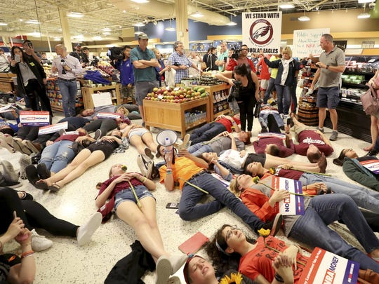 """Demonstrators lie on the floor at a Publix Supermarket in Coral Springs, Fla., Friday, May 25, 2018. Students from the Florida high school where 17 people were shot and killed earlier this year did a """"die in"""" protest at the supermarket chain that backs a gubernatorial candidate allied with the National Rifle Association. Shortly before the the """"die-in"""" Publix announced that is will suspend political donations."""