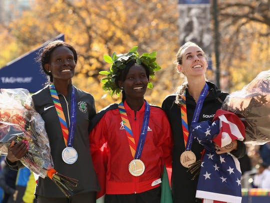 First-place finisher Mary Keitany, center, second-place finisher Sally Kipyego, left, and third-place finisher Molly Huddle celebrate with their medals after the 2016 New York City Marathon.