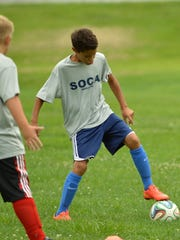 Braden White steals the ball from a player during a practice on Monday, August 10. White is on the SOCA Boys' Under-12 team.