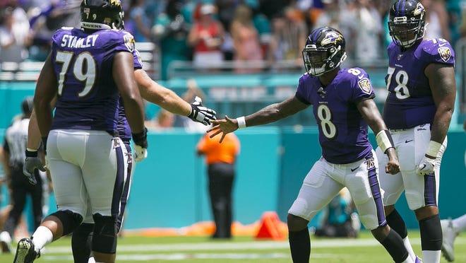 Baltimore Ravens quarterback Lamar Jackson (8), celebrates throwing for a touchdown against the Dolphins Sunday Sept 8, 2019, at Hard Rock Stadium in Miami Gardens. (BILL INGRAM/palm beach post]