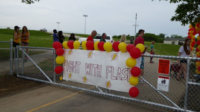 """A sign reading """"Fight With Flash"""" hangs at the entrace to the West High athletic fields Friday for the inaugural Flash Festival!, organized by the West High School Dance Marathon organization."""
