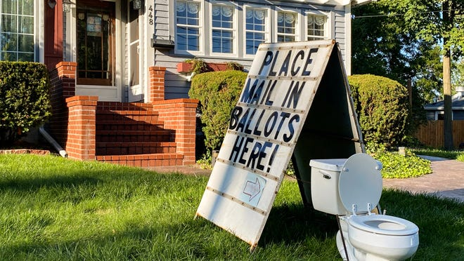 A political display is set up in the lawn of a home on West Columbia Street in Mason, Mich., on Friday, Sept. 18, 2020.  Barb Byrum, the Democratic clerk of Ingham County, filed a complaint with police over the display, saying it could mislead people who aren't familiar with how mail-in voting works.
