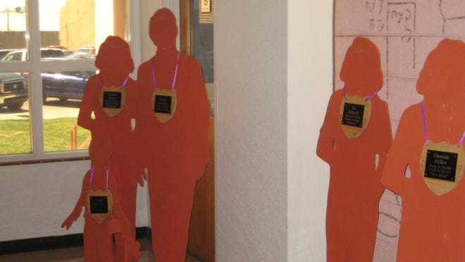 Wood cutouts line the 12th Judicial District Courthouse lobby as part of Crime Victims' Awareness Week.