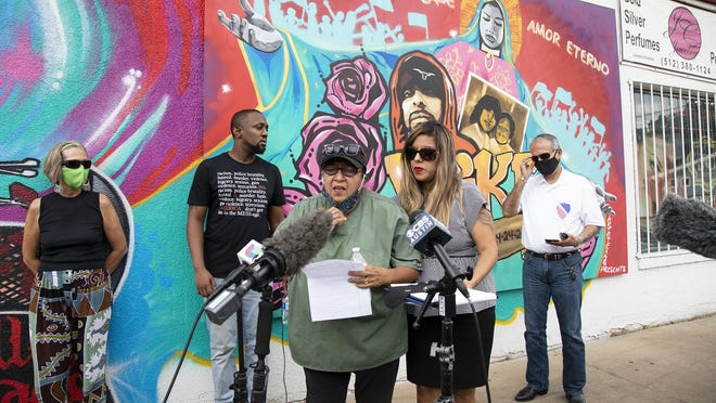 Brenda Ramos, center, stands in front of a recently painted mural of her son Michael Ramos while speaking during a press conference on July 28. Michael Ramos was shot and killed by an Austin police officer in April.