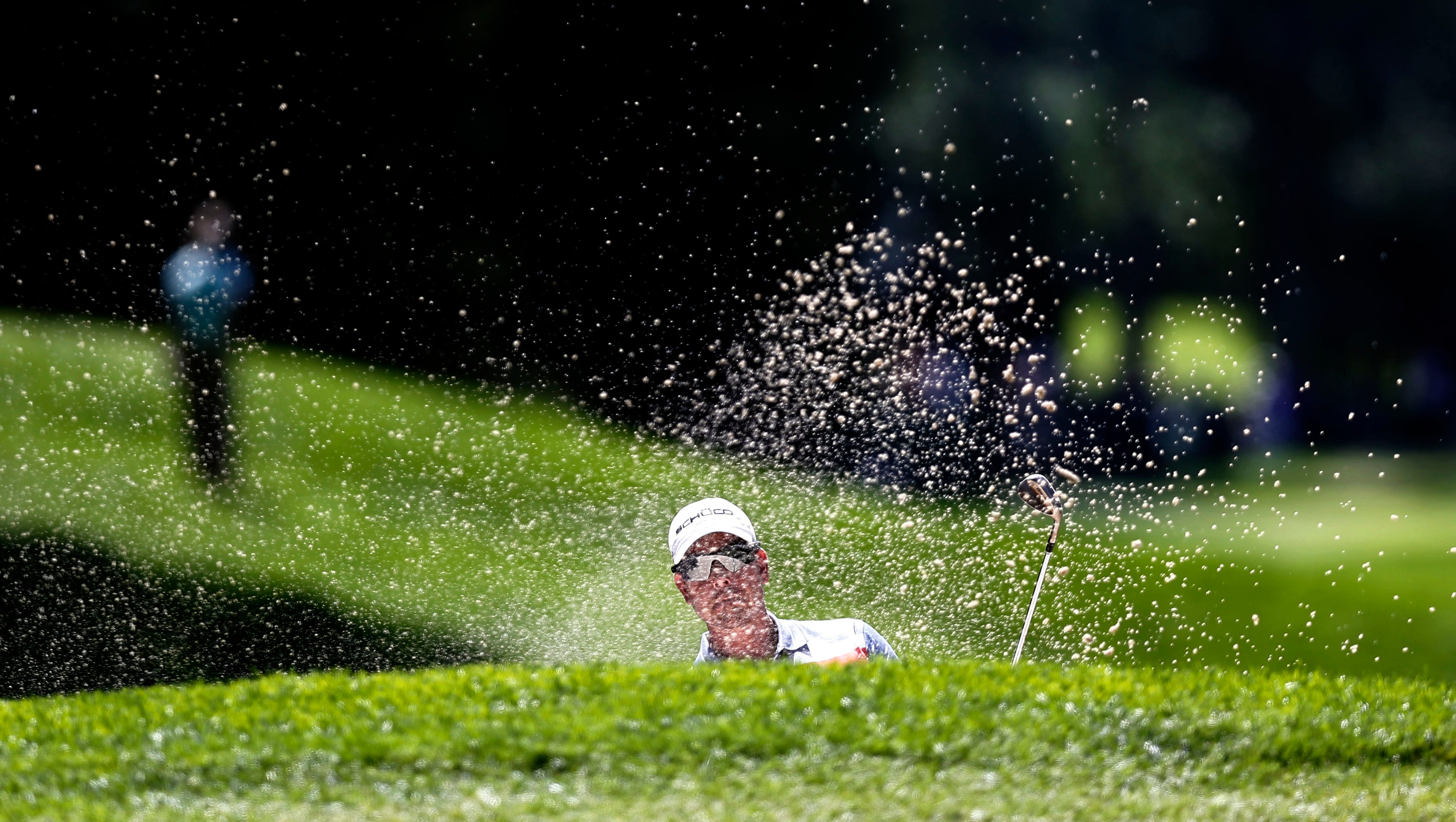 Henrik Stenson plays from a greenside bunker at No. 2.