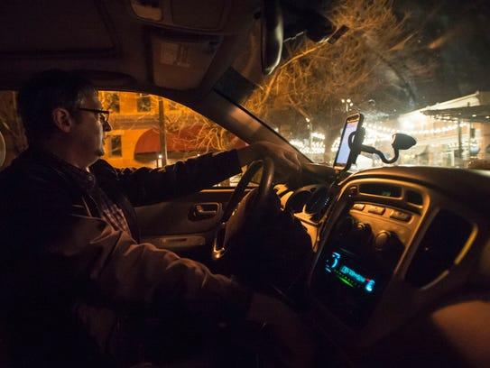 Uber and Lyft driver Scott Saathoff waits for passengers