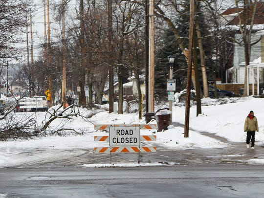 A road remains closed five days after the December 2013 ice storm. Many Board of Water & Light customers were without power for nearly two weeks.