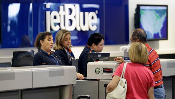 JetBlue Airways ticket agents assist passengers Oct.