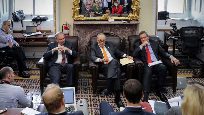 In this Nov. 8, 2017, photo, from left, Sen. Tim Kaine, D-Va., Senate Minority Leader Chuck Schumer, D-N.Y., and Sen. Mark Warner, D-Va., speak informally on tax reform and the elections with reporters in the Senate Press Gallery at the Capitol in Washington. It's an article of faith among Republicans that the GOP's electoral fortunes next year hinge on whether they succeed in their longstanding dream to redraft the nation's complex, inefficient tax code.