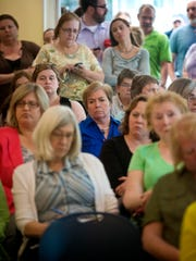 A standing-room-only crowd listens as a committee of state legislators takes testimony on the Department for Children and Families in Winooski on Thursday.
